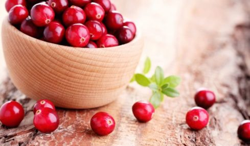A bowl of fresh cranberries on a wooden board.