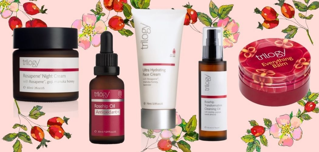The suite of Trilogy rosehip products against a pink background with flowers.