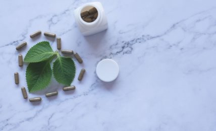 A pill bottle and a heart shape made of pills, surrounding three leaves set in a heart shape, on a marble counter. Represents vitamin K supplements